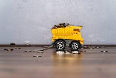 Negocio y concepto del dinero - camión con un cuerpo completo de monedas Fotografía de archivo
