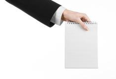 Negocio y tema del reportero: la mano de un periodista en un traje negro que sostiene un cuaderno con un lápiz en un fondo blanco Foto de archivo libre de regalías