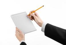 Negocio y tema del reportero: la mano de un periodista en un traje negro que sostiene un cuaderno con un lápiz en un fondo blanco Fotografía de archivo