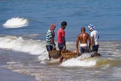 Fishermen carrying fish in baskets. Stock Photos