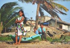 NEGOMBO, SRI LANKA, im Februar 2013: Smal-Mädchen im bunten Kleid, das vor Boot auf Strand steht Zwei kleine Jungen, die auf dem  Stockbilder