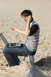 Negotiating a deal. Young professional working on the beach talking to a client Royalty Free Stock Images