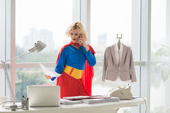 Negotiating by phone. Angry superwoman reading document when negotiating by phone Stock Photos