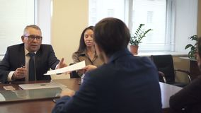 Negotiation briefing with multiethnic partners in office conference room. Lawyer giving contract draft to mature businessman and african-american businesswoman stock video