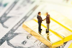 Negotiation, collaboration in investment, gold, wealth management concept, miniature people businessman handshaking on gold royalty free stock images