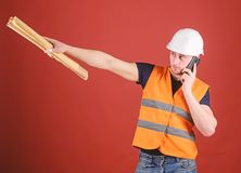 Negotiation concept. Man, architect in helmet supervises construction on phone, red background. Engineer, architect. Builder on busy face speaks on smartphone royalty free stock photos
