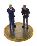 Negotiation. Two small businessmen negotiate on a Euro-Coin Royalty Free Stock Photography
