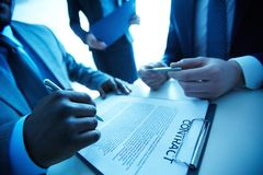 After negotiations. Image of contract on workplace and group of partners making decision to sign it Stock Photography