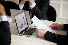 Negotiations under contract at meeting of three partners, close. Businessman hands holding document considering deal buying startup with project statistics on Royalty Free Stock Image