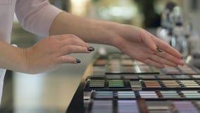 Negozio cosmetico, ombretto scelto della donna del compratore dalla tavolozza dei colori differenti per trucco luminoso ed applic video d archivio