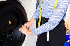 Negozio della lavanderia facendo uso della macchina per pulir a seccoe Immagini Stock Libere da Diritti