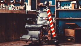 Negozio di barbiere Palo Logo del parrucchiere, simbolo Barber Chair d'annata alla moda Parrucchiere nell'interno del parrucchier immagini stock libere da diritti