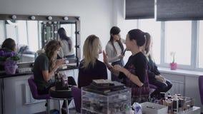 Negozio di bellezza Tre modelli nel negozio di bellezza Le ragazze preparano per esposizione alla moda Il truccatore fa un compen stock footage