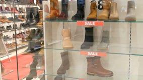 Negozio di scarpe di vetro della vetrina su cui la vendita dell'iscrizione Scarpe alla moda di autunno-inverno sul contatore del  video d archivio
