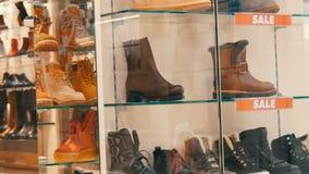 Negozio di scarpe di vetro della vetrina su cui la vendita dell'iscrizione Scarpe alla moda di autunno-inverno sul contatore del  archivi video