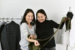 Negozio di vestiti, stilista asiatico che lavora nel suo studio della sala d'esposizione, sarto da donna che abbina il migliore c immagine stock