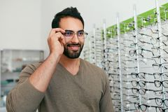 Negozio di vetro Uomo che prova sugli occhiali nel deposito di ottica immagine stock