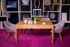 Negozio, vendita di mobilia in un centro commerciale Campione dell'esposizione che pranza tavola di legno con le sedie del tessut fotografie stock