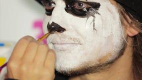 Negro de la nariz del ` s del hombre de la pintura de la mano del artista en Halloween almacen de metraje de vídeo