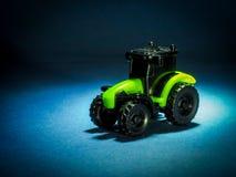 Negro del tractor de la maquinaria agrícola y verde en un fondo oscuro foto de archivo libre de regalías