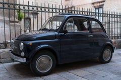 Negro el cinquecento 500 del vintage de Fiat aparcamiento delante de las verjas fuera de la iglesia en Puglia, Italia meridional foto de archivo