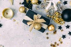 Negro y decoraciones de la Navidad del oro con la caja de regalo Imagenes de archivo
