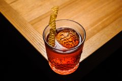 Negroni in crystal glass with dried honeycombs. Alcoholic cocktail staying on the corner of table in crystal glass with dried honeycombs stock photos
