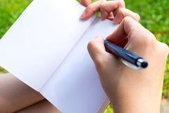 Nehmen der Kenntnis mit Stift und Buch Stockbild