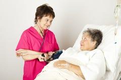 Nehmen des Blutdruckes im Krankenhaus Stockfotografie