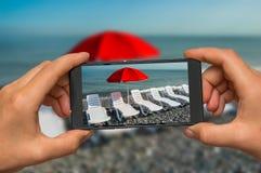 Nehmen des Fotos der ein Sonnenbad nehmenden Betten und des roten Regenschirmes mit Telefon Lizenzfreies Stockfoto