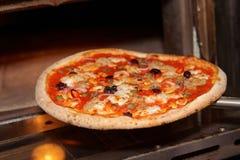 Nehmen einer Pizza aus Ofen heraus Stockbilder