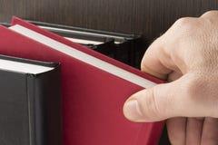 Nehmen eines Buches Stockfotografie