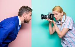 Nehmen eines Porträts Gesch?ftsmann, der vor weiblichem Fotografen aufwirft Modeschie?en im Fotostudio H?bsche Frau lizenzfreies stockfoto