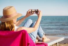 Nehmen eines selfie an ihrem Telefon am Strand Stockbilder