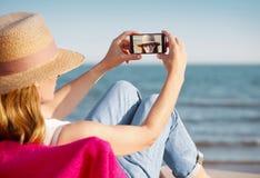 Nehmen eines selfie an ihrem Telefon am Strand Stockfoto