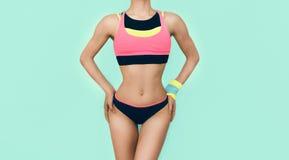 Nehmen Sie athletisches Mädchen in der hellen modischen Sportkleidung auf blauem backgr ab Stockbilder