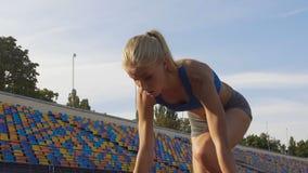 Nehmen Sie den blonden Athleten ab, der auf dem Sportfeld läuft und vor Wettbewerb ausbilden, LangsammO stock video footage