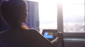Nehmen Sie die hübsche Frau ab, die zu Hause auf dem Fahrradsimulator durch das Fenster übt, das auf der Stadt während des Sonnen Stockbild