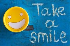 Nehmen Sie ein Lächeln Motivaufschrift Stockfoto