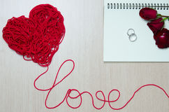 Nehmen Sie ein rotes Garn in Herzform und in Benennungsliebe mit roten Rosen Lizenzfreie Stockfotografie