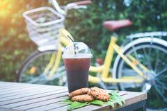 Nehmen Sie einen schwarzen Kaffee und braunen Plätzchen mit gelbem Fahrrad am Th stockfoto