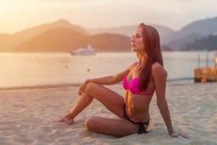 Nehmen Sie gebräuntes Modell im Bikini ab, der auf sitzendem Sand des Strandes angesichts des Morgens bei Sonnenaufgang mit Berge stockfotografie