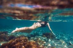 Nehmen Sie Schwimmen der jungen Frau im Ozean, Unterwasserfoto ab Stockfoto