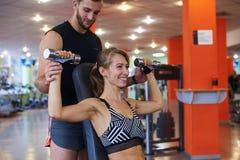Nehmen Sie sportliche Frau mit dem Trainer ab, der Muskeln in der Turnhalle biegt Stockfotografie