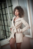 Nehmen Sie tragenden weißen Mantel des jungen Mode-Modells im Fensterrahmen ab Reizende sexy moderne Frau mit dem hellbraunen gel Stockbild