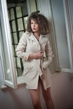 Nehmen Sie tragenden weißen Mantel des jungen Mode-Modells im Fensterrahmen ab Reizende sexy moderne Frau mit dem hellbraunen gel Lizenzfreie Stockfotografie