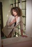 Nehmen Sie tragenden weißen Mantel des jungen Mode-Modells im Fensterrahmen ab Reizende sexy moderne Frau mit dem hellbraunen gel Stockbilder
