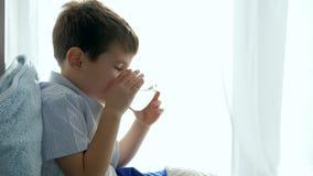 Nehmen von Pillen, von Heilung des Kindes mit Abhilfe und von Glas Wasser im Glas in den Händen auf Fensterbrett stock video footage