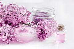 Nehmenbad mit der lila Kosmetik eingestellt und Blüte auf weißem Tabellenhintergrund Stockfotos