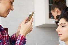 Nehmendes Vorlagenfoto des Salons auf Smartphone der Schönheitsfrau beim Make-up an setzen und Herstellung von hairdro Lizenzfreie Stockfotos